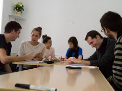 Photo of 3 groups of students speaking in a classroom