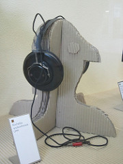 Photo of headphones on cardboard cutout head