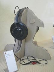 Photo of headphones on cardboard cutout head